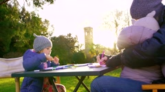 Mother with her two little daughter sit at table and draw with colored markers Stock Footage