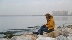 Woman sitting at the sea  side and using smart phone Stock Footage
