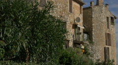 A tree next to stone buildings in Tourrettes-sur-Loup Stock Footage