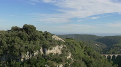 Pan view of the Roman Bridge and the buildings of Tourrettes-sur-Loup Stock Footage
