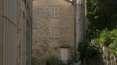 Woman walking on a picturesque narrow street in Tourrettes-sur-Loup Stock Footage