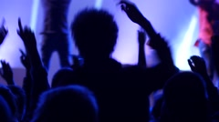 Jumping fan spectator silhouettes on concert lumiere cheerfully dancing hands Stock Footage