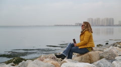 Woman sitting at the sea side and drinking coffee Stock Footage