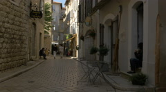 People walking and relaxing on a paved street in Vence Stock Footage