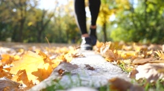 Girl legs shues walking on the curb in autumn park with fallen leaves - stock footage