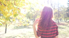 Teen girl walk in an autumn park nature sun light haze in slow motion back cam Stock Footage