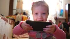 Happy little kid girl watch cartoons via smart phone in sun light haze Stock Footage