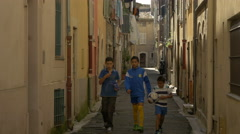 Three kids walking on a street in Vence - stock footage