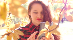 Young smile red head girl take a shot via smart phone of yellow autumn leaves Stock Footage