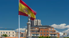 Spanish flag waves behind statue of Christopher Columbus timelapse, plaza de Stock Footage