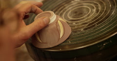 Stock Video Footage of Close-up shot of a young woman at workbench painting ceramics in pottery studio.