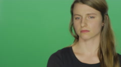 Young women looks sad and cries, on a green screen background Stock Footage