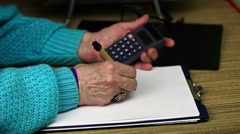 Old woman writes and use calculator Stock Footage