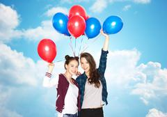 Happy teenage girls with helium balloons Stock Photos