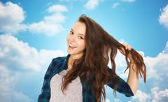 Happy teenage girl holding strand of her hair Stock Photos
