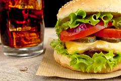 Big single cheeseburger with glass of cola on wooden desk on black background - stock photo