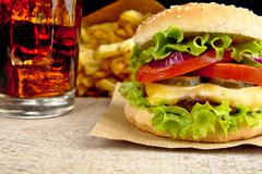 Big single cheeseburger with glass of cola and french fries on wooden desk on Stock Photos