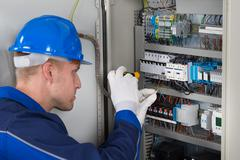 Male Electrician Working On Fusebox With Screwdriver - stock photo