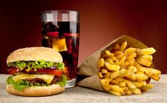 Stock Photo of Cheeseburger with glass of cola and french fries on red spotlight background