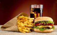 Cheeseburger with drink of cola, french fries on red spotligh Stock Photos