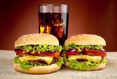Two cheeseburgers with glass of cola on wooden desk on red background - stock photo