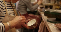 4K Workers in a pottery studio applying decorative glaze to tea & coffee cups. Stock Footage