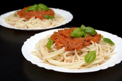 Two dish pasta with bolognese sauce for supper on black background - stock photo