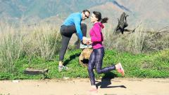 Young woman jogging, man doing laces on the trunk in the mountains Stock Footage