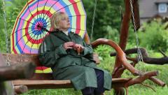 Woman in green raincoat and with umbrella sits on the swing bench - stock footage