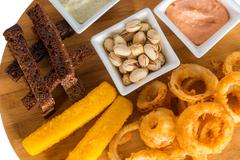 Cheese sticks, onion rings, crackers, salted peanuts and sauce Stock Photos