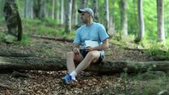 Man with white Tablet PC sits on a fallen tree in the wood and listens to music Stock Footage