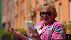 Woman sits on the bench and communicates via smartphone Stock Footage