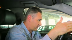 Angry man in the car pissed off by drivers in front close up Stock Footage