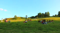 Young people sitting on the grass in the city park rr Stock Footage