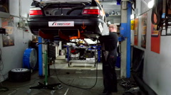 A mechanic is using a grinder on a race car Stock Footage