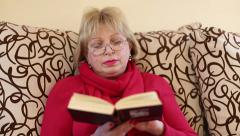 Woman sits on a divan and reads a book - stock footage