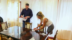 Husband and wife setting dining table in the house - stock footage