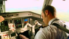 Pilots in the cockpit operate with commercial airplane in flight Stock Footage
