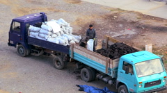 Workers load coal into a sack on the truck Stock Footage