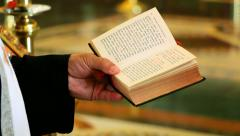 Priest read a prayer from the book in the church Stock Footage