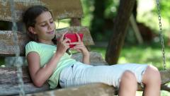Girl with red smartphone sits on swing bench in the garden and listens to music Stock Footage