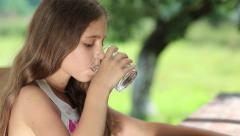Girl drinks water from a glass Stock Footage