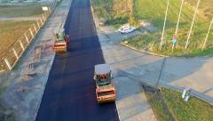 Asphalt paving. Rollers machines working on fresh asphalt aerial shoot Stock Footage