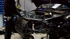 Mechanic repairing a black car in the service garage Stock Footage