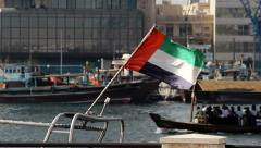 UAE flag fly on wind, flagpole attached to boat, Abra ferry move blurred on back Stock Footage