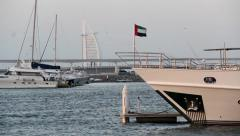Large modern yacht rostrum, UAE flag on wind, dusk, Burj Al Arab on back Stock Footage