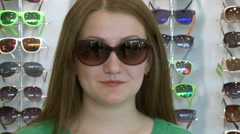 Woman trying on glasses in the store . Stock Footage