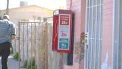 People Walk by Red Pay Phone in Border Town Stock Footage