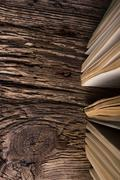 Top view of old book stack over old grunge natural wooden shabby - stock photo