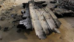 Charred wreckage of wood vessel on shore, part of hull stay against aground - stock footage